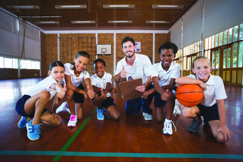 Kids enjoying their school gymnasium by playing a game of basketball.