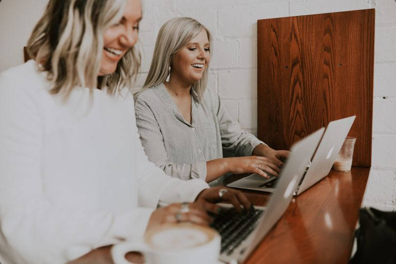 two women in business attire using laptops and smiling