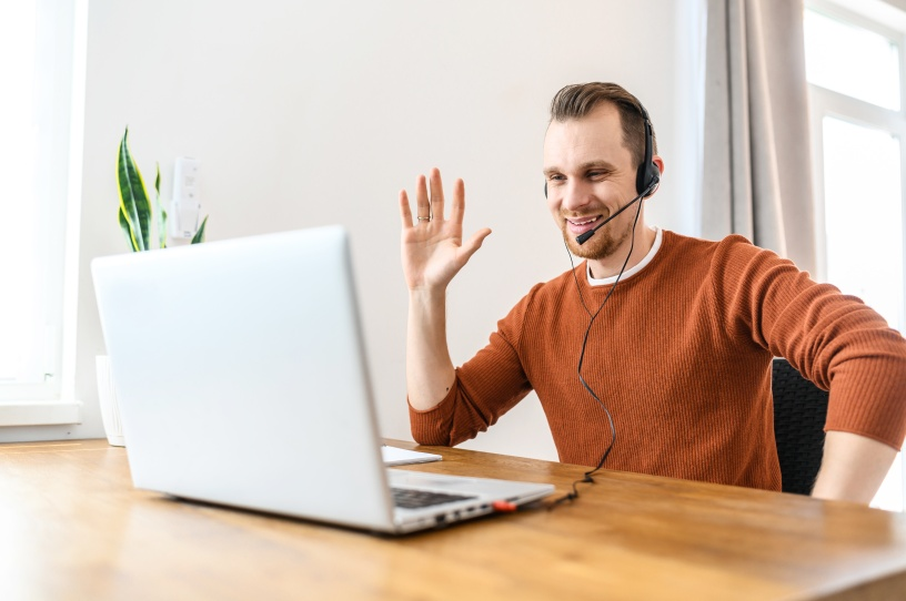 Video connection, video call. Young attractive guy says hello to the laptop webcam and smiles